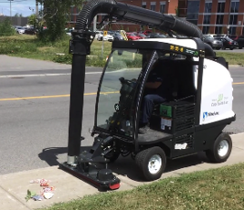 Madvac sweeper cleans pedestrian path in front of large brick building