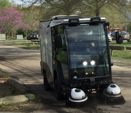 Madvac compact sweeper cleaning small alley in front of trees